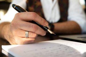 Füller in der Hand einer Person vor einem Blatt Papier